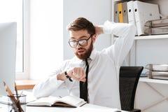 Szokujący młody biznesmen patrzeje zegarek zdjęcia stock