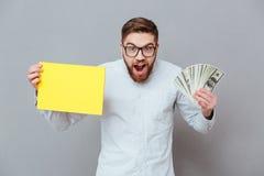 Szokujący uśmiechnięty biznesmena mienia copyspace pieniądze i puste miejsce Zdjęcia Stock