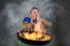 Szokujący upaćkany mężczyzna z fartucha mienia niecką w pożarniczym paleniu jedzenie w kuchennej katastrofie i okropnym niewprawn obraz royalty free