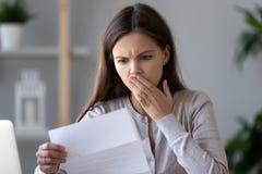 Szokuję stresował się młodej kobiety czytania dokumentu list o długu zdjęcia stock
