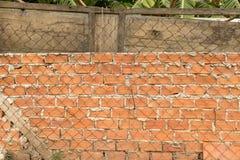 Szorstka ściana z cegieł z Ośniedziałym Drucianym ogrodzeniem i Stary Drewniany drzwi w ogródzie obraz stock