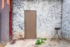 Szorstka betonowa ściana z Drewnianym drzwi i Pożarniczym pochodnia stojakiem fotografia royalty free