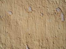 Szorstki beżowy kolor żółty malująca ściana z srogimi cieni pęknięciami i obieranie seansu cementem pod zdjęcia stock