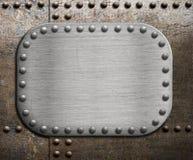 Szorstki kruszcowy talerz nad ośniedziałym metalu tłem Obrazy Stock