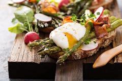 Szparagowy i bekonowy bruschetta z kłusującym jajkiem zdjęcia stock