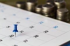 Szpilka na kalendarzu na 20th miesiąc z zamazanymi monetami Zdjęcia Stock