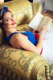 Szpilka W górę dziewczyny z książką na krześle Zdjęcia Stock