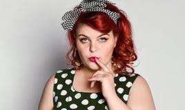 Szpilka w g?r? ?e?skiego portreta Piękna retro kobieta w polki kropki sukni z czerwonymi wargami stawia palec jej wargi zdjęcia royalty free