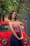 Szpilki dziewczyna pozuje na czerwonym rosyjskim retro samochodowym tle Figlarnie spojrzenie załatwiający na kamerze obraz stock