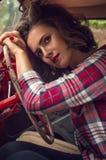 Szpilki dziewczyna w szkockiej kraty koszula wearily opierał na jej rękach, trzyma kierownicę w salonie stary czerwony retro ca zdjęcia stock