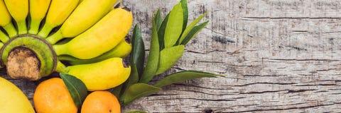 SZTANDAR, Długiego formata Kolorowe owoc na białym drewnianym stole, banany, carambola, mango, melonowiec, mandarynka, bliźniarka zdjęcia stock