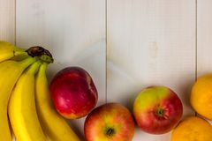 SZTANDAR, Długiego formata Kolorowe owoc na białym drewnianym stole, banany, carambola, mango, melonowiec, mandarynka, bliźniarka zdjęcia royalty free