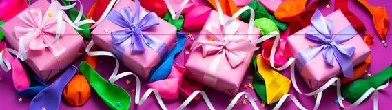 Sztandaru Dekoracyjny pudełkowaty skład z prezenta łęku atłasowych tasiemkowych nadmuchiwanych piłek tła A wężowatym purpurowym o zdjęcia stock