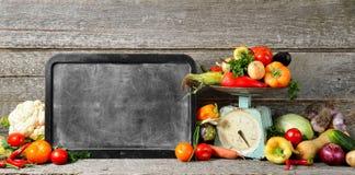 Sztandaru skład surowi organicznie świezi warzywa, kredowa deska dla teksta, równowaga na drewnianym stole Zdjęcie Royalty Free