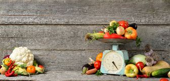 Sztandaru skład surowi organicznie świezi warzywa, równowaga na drewnianym brązu stole Zdjęcie Royalty Free