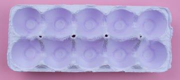 Sztandaru stojak dla jajek purpurowych na różowym tle Obrazy Stock