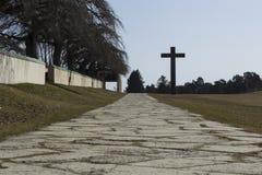Sztokholm, Szwecja/- 14 Febrary 2018: Drogowy prowadzić do granitowego krzyża, przy UNESCO światowym dziedzictwem lasu cmentarz Obrazy Royalty Free