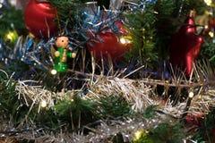 Sztuczna choinka dekorująca z drewnianą figurką, dekoracją dla choinki, światłami, świecidełkiem i girlandą, czerwone piłki fotografia stock