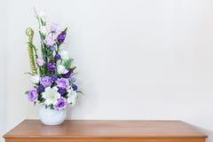 Sztucznego kwiatu waza na drewnianej stołu i bielu ścianie Zdjęcie Stock