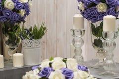 Sztuczni kwiaty w wazie i candlesticks w candlesticks dla romantycznej atmosfery zdjęcia stock