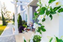 Sztuczny bluszcz z białymi kwiatami wokoło filaru z domem Fotografia Stock