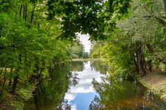 Sztuczny jezioro w zielonym obfitolistnym parku z odzwierciedlającą powierzchnią woda Fotografia Stock