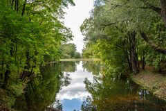 Sztuczny jezioro w zielonym obfitolistnym parku z odzwierciedlającą powierzchnią woda Zdjęcie Stock