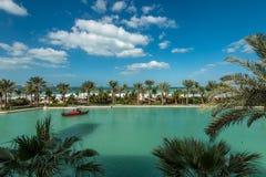 Sztuczny kanał z tradycyjnym Arabskim łódkowatym abra, palmą i plażą, zdjęcia stock