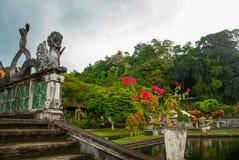 Sztuczny most z cztery statuami smoki z kręconymi ogonami, Tirta Gangga park, Karangasem, Bali, Indonezja obraz stock