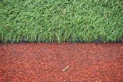 Sztuczny zawody atletyczni z zieloną trawą łączył z sztuczną trawą zdjęcia stock