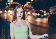 Sztuka portret piękny imbirowy włosiany dziewczyna portret w nocy mieście zaświeca Uliczny moda stylu portret potomstwa zdjęcia royalty free