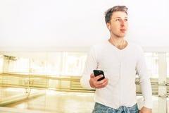 Sztuka współczesna tancerz ubierał w biel ubraniach słuchający muzykę z smartphone używać w lustrzanej sala hełmofony obraz royalty free