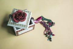 Sztuki biżuterii pudełko z szkarłatnym kwiatem na fiołkowym tle Obraz Royalty Free