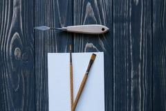 Sztuki i rzemiosła narzędzia Artysty ` s muśnięcie, kanwa, paleta nóż na ciemnym nieociosanym tle Obraz Stock