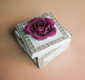 Sztuki pudełko dla biżuterii z szkarłatnym kwiatem na beżowym tle Zdjęcia Stock