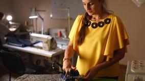 Szwaczki kobieta dekatyzuje woolen smokingowego płótno i używać profesjonalisty żelazo w krawieckim warsztacie Żeńska ręka trzyma zbiory wideo