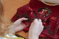 Szwaczki obsiadanie przy stołem i haftuje czerwoną kamizelkę z koralikami w studiu obrazy royalty free