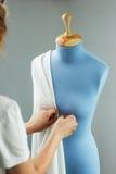 Szwaczki pomiarowa piękna tkanina na błękita krawczyny atrapie w jej warsztacie Obraz Stock