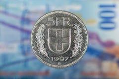 5 Szwajcarskiego franka moneta z 100 Szwajcarskimi frankami Bill jako tło Zdjęcie Royalty Free