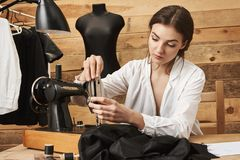 Szwalna maszyna musi taktująca stosownie Skupiający się żeński projektant szy odzieżowego w warsztacie, stawia nić w nasadce Zdjęcia Stock