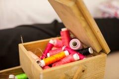 Szwalne nici stubarwne w drewnianego pudełka tła zbliżeniu Obraz Stock