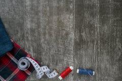 Szwalni akcesoria, cajgi i szkockiej kraty tkanina na ciemnym drewnianym tle, Tkanina, centymetr, szwalny nici, igielnego i szwal zdjęcie stock