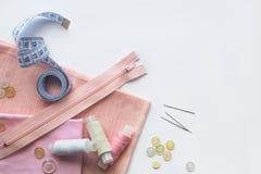 Szwalni akcesoria i różowa tkanina na białym tle Tkanina, szwalne nici, suwaczek, igła, guziki i szwalny centymetr, zdjęcie royalty free