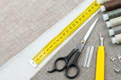 Szwalny deseniowy skład z nożycami, cewy nić, szpilki, pomiarowa taśma fotografia stock