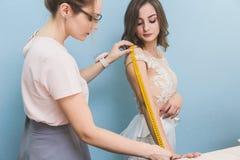 Szwalny warsztat ręki target3574_1_ miarę szwaczki pracy Szwaczka bierze pomiary ślubna suknia zdjęcia royalty free