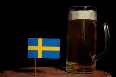 Szwedzi flaga z piwnym kubkiem na czerni Obrazy Stock