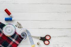 szy? wyposa?enia Szkockiej kraty tkanina na białym drewnianym tle Tkanina, szwalne nici, igła, szpilki, nożyce i szyć, obrazy royalty free