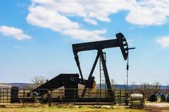 Szyb naftowy pompy dźwigarki sylwetka w metali bydło ono fechtuje się z błękitnymi wzgórzami w dystansowym i ładnym niebieskim ni obrazy royalty free