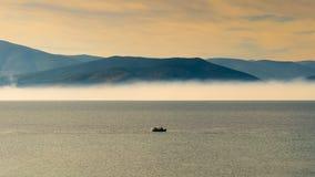 Szybki łódkowaty podróżowanie przeciw dramatycznemu niebu i ranek mgle jako tło Zdjęcia Stock
