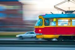 Szybki poruszający czerwieni i koloru żółtego tramwaj w mieście z światłami dalej obrazy royalty free